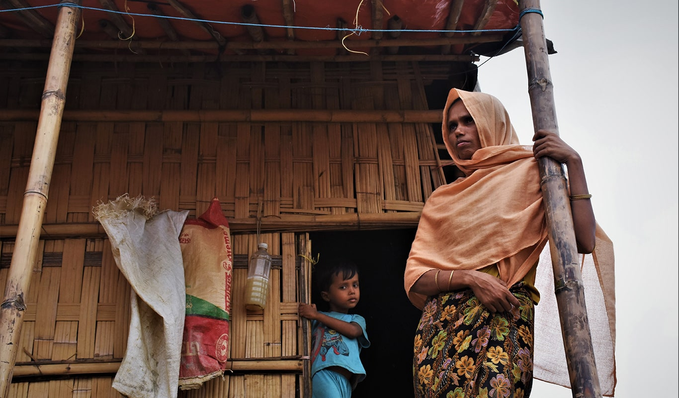 Women in an orange headscarf and her sun standing in front of their shelter in Bangladesh