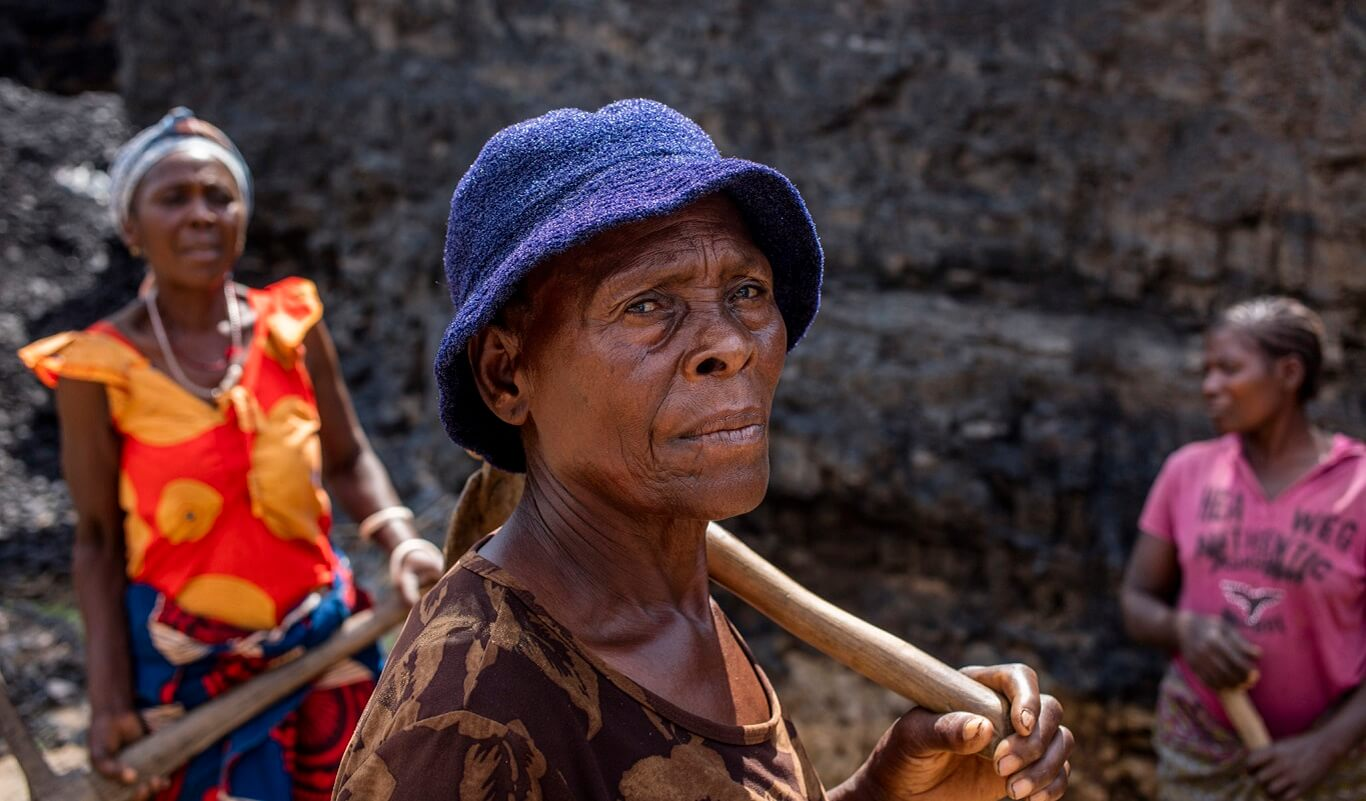 An elderly black woman in a blue hat stands with a pickaxe over her shoulder and a serious look on her face.