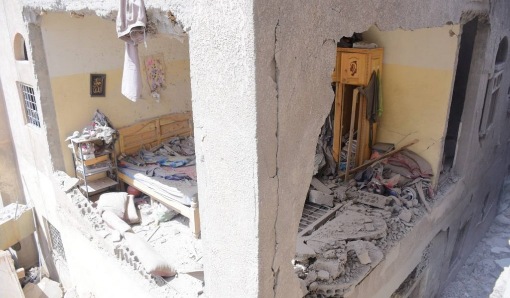 The image shows the inside of a bedroom in San'a that was destroyed by bombing. There is rubble all over the bed, and the external walls have crumbled away.
