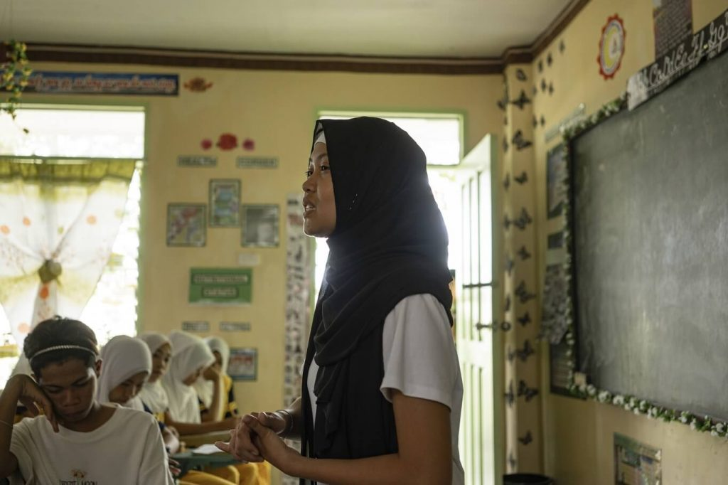 A youth leader, who is a Muslim Filipino woman stands at the front of a classroom talking to other young women about ending child marriage.