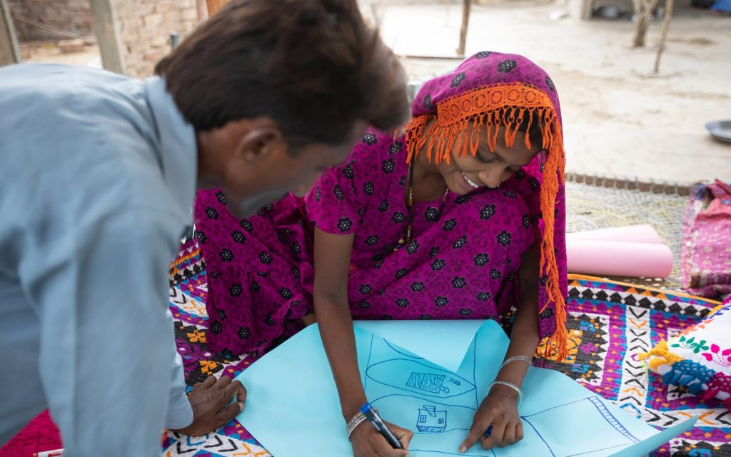 A woman in a pink shawl drawing diagrams on a blue chart paper